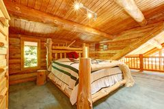 Log cabin bedroom under wood large ceiling. Stock Photography
