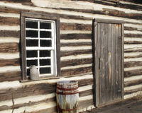 Log cabin door window close-up. Close-up angle view of a log cabin door and window, with an old barrel and jug Royalty Free Stock Photos