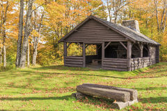 Log Cabin among Fall Foliage. An old log cabin in Vermont surrrounded by colorful fall foliage Royalty Free Stock Image