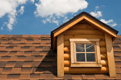 Log cabin gable and roof. A closeup view of a gable or dormer window on the roof of a small log cabin Stock Image