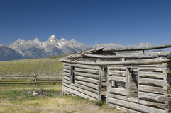 Log Cabin at the Grand Tetons. An old weathered log cabin slowly deteriorates under the Wyoming summer sun against the backdrop of the Grand Teton mountains stock photos