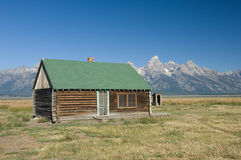 Log Cabin at the Grand Tetons. An old log cabin and outhouse sit along on a prairie in Western Wyoming against the backdrop of the Grand Teton mountain range royalty free stock photos