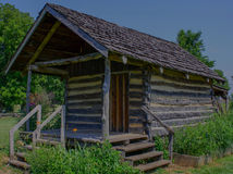 Log Cabin and green foliage under and around. Royalty Free Stock Photo