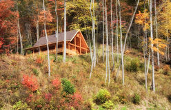 Log Cabin on a Hill. Pretty log cabin in the mountains during the autumn season Royalty Free Stock Photos