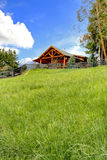 Log cabin on the hill with fresh green grass. Stock Image