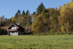Log cabin on hillside. Scenic view of log cabin on green hillside with forest in background stock photography