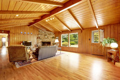 Log cabin house interior. Living room with fireplace and leather