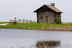 Log cabin on lake. Old log cabin with wooden fence on the edge of a lake Stock Images