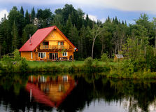 Log Cabin On A Lake. A beautiful log cabin on a lake, with reflections in the water royalty free stock photography