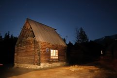Log Cabin at Night. A log cabin at night in Baihaba, the most north-western village of China, bordering Kazakhstan Stock Photo
