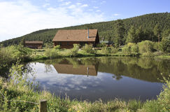 Log cabin by pond. Rural residential log cabin beside a blue lake or pond with reflection Stock Photos