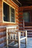 Log Cabin Porch. Wooden chair sitting on porch of rustic log cabin Stock Photography