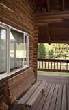 Log cabin porch. Wooden bench on the porch of a rustic log cabin Stock Photos