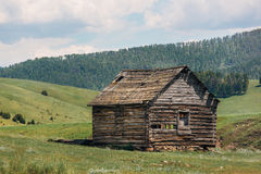 Log Cabin Ruin. The old ruins of a log cabin in a rural valley Stock Photography