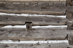 Log cabin sawn logs to corner closeup with snow in between. A festive winter background with weathered silvery grey horizontal sawn logs with snow in between Royalty Free Stock Image