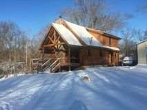 Log cabin in the snow. Winter day in the Stock Photos