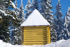 Log cabin in snowy forest. Winter in Carpathians Royalty Free Stock Photography