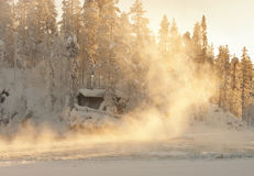 A log cabin and steaming water in the sun stock images