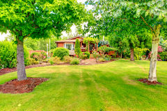 Log cabin style house exterior with front yard landscape Royalty Free Stock Photography