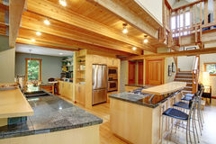 Log cabin style. Kitchen interior. View of shiny kitchen with steel appliances, light wooden cabinets and ceiling beams. View of bar with stools and counter top Royalty Free Stock Photography