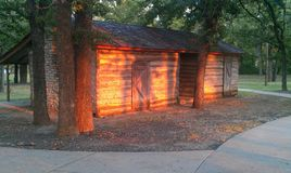 Log Cabin at Sunset. This is in Holland Lake Park in Weatherford Texas. There are a couple of Fountains in the lake, and a play area for kids. There is a nice Stock Images