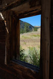 Log Cabin View. Mountain view through old abandoned log cabin window Royalty Free Stock Images