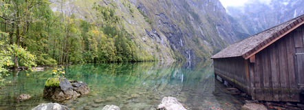Log cabin and water in Obersee,koenigssee. Log cabin stand in the shore of Obersee, a heaven style view Royalty Free Stock Images