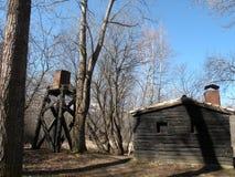 Log cabin and water tank Stock Photos