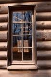 Log cabin window. Reflections in a log cabin window in Winter Stock Photo
