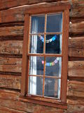 Log cabin window with small prayer flags. Log cabin window showing small prayer flags strung inside Royalty Free Stock Photo