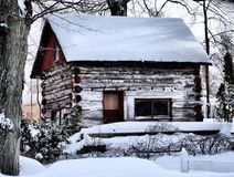 Log cabin in winter. Scenic view of rural log cabin covered with snow in wintertime Royalty Free Stock Images