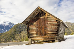 Log cabin in a winter landscape. With a light covering of fresh white snow in the ground and distant snow-covered mountain peaks Stock Image