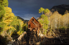 Log cabin in woods. With dark stormy sky stock images