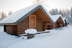 Log cabins. A photo of four small log cabins in row at snowy winter day Royalty Free Stock Photos