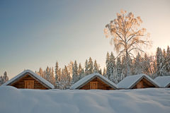 Log cabins. A photo of small log cabins in row at snowy winter day royalty free stock photography