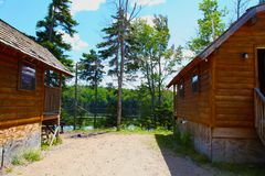 Log cabins in the woods by a lake. Campground showing two lakeside log cabins in the Adironacks stock images