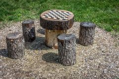 Log Chessboard and log stools. Log Chessboard with log stools on wood chips in a grassy park Stock Photography