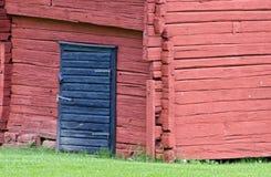 Log de madeira vermelho com porta azul Fotografia de Stock