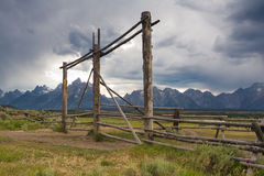 Log fence and Teton Mountains. Rustic rail fence from Lodgepole pine frames the Teton Mountains as summer afternoon thunderstorm rolls in over jagged peaks Royalty Free Stock Images