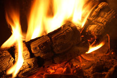 Log on fire. With flames in yellow Royalty Free Stock Photography