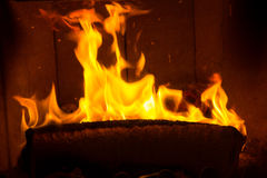 Log on fire burning billets in fireplace Stock Photos