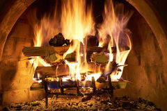 Log Fire. A log fire burning furiously in a stone fire place Royalty Free Stock Photo
