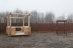 Log gazebo in frozen garden in mist Stock Photos
