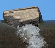 Log hanging on the edge. Water logged fall Stock Images