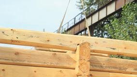 Build a house from logs. A log is hoisted with a crane to build a house stock video