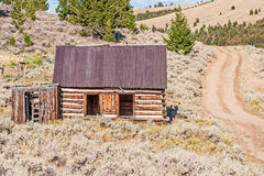 Log Home Beside a Dirt Road Stock Photography
