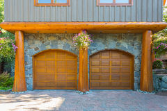 Log house. Beautiful modern log house in the mountains in Canada. Two door garage, wooden Royalty Free Stock Photos