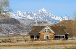 Log House on Prarie. Log House With Snow Covered Mountains in Background Royalty Free Stock Photos