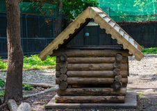 Log-hut. Small wooden house for animals in the aviary reserve Stock Image