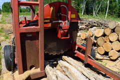 Log Slasher with Freshly Cut and Piled Wood Royalty Free Stock Photos